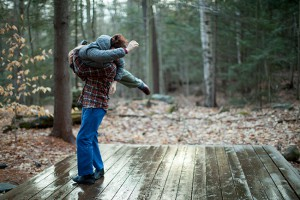 Two dancers doing a lift on a wooden stage in the woods