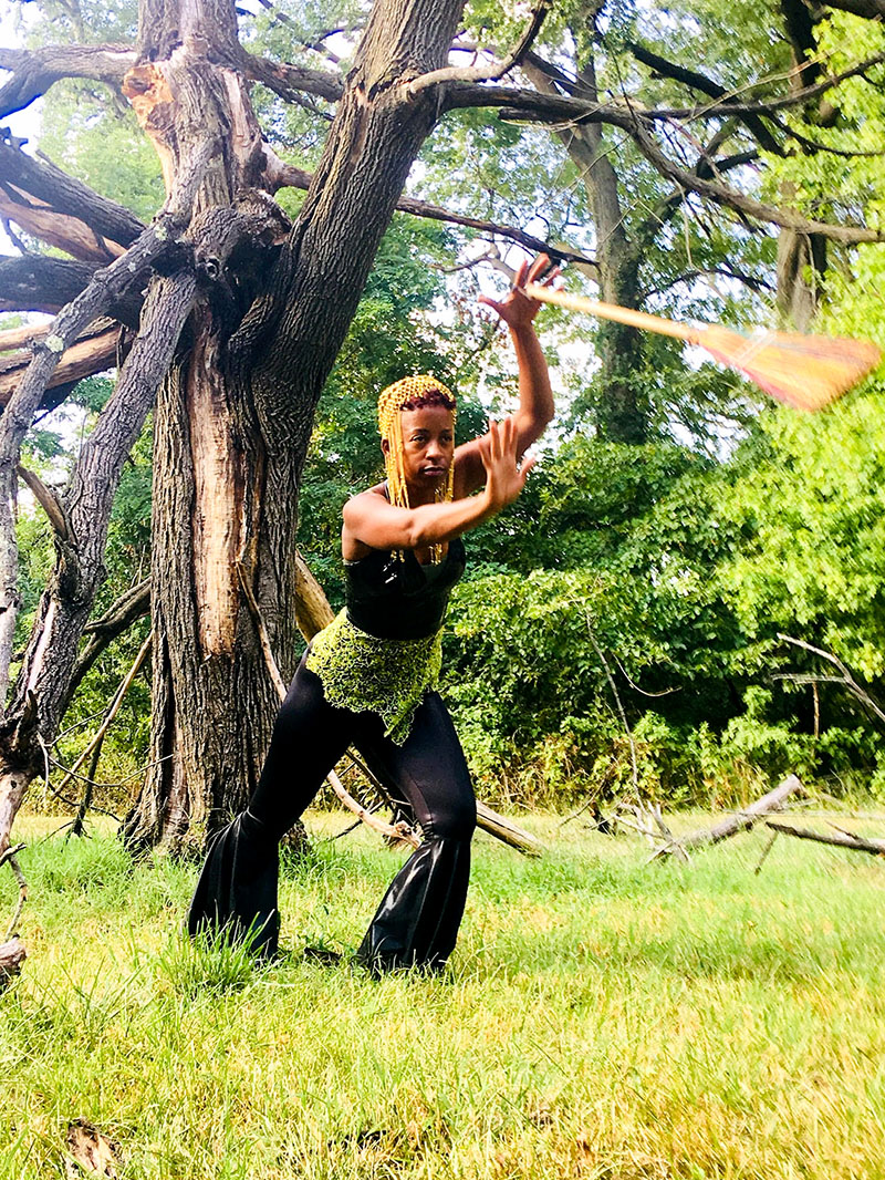 Photo of Donne Lewis dancing with broom in forest
