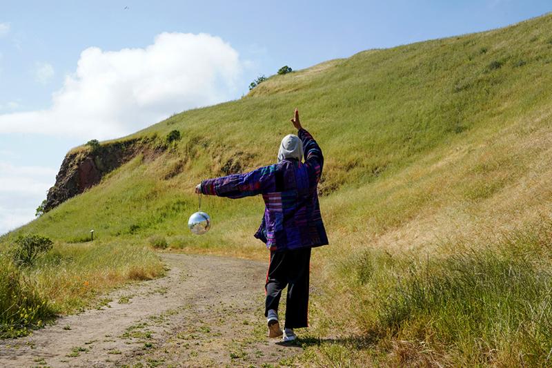 estrella/x holding a disco ball on a hillside
