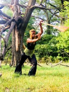 Donne Lewis dancing under tree with broom