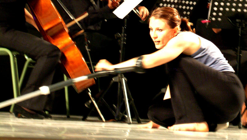 Nadia crouched low with her crutch in front of a cello