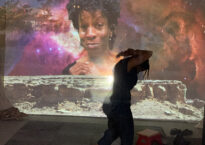 Danielle dancing with her face projected on the wall behind her
