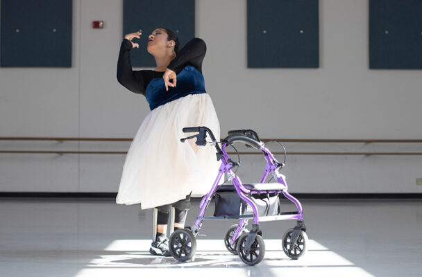 Vanessa Cruz in white long tutu dancing next to her walker
