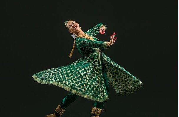 Charlotte Moraga dancing in a swirling green and gold dress