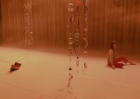 Georgie Goater sitting on a stage with beads hanging